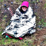 hiker wrapped up in emergency blanket